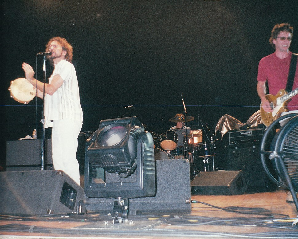 A rock band, Pearl Jam, performing onstage. A vocalist sings into a microphone while playing tambourine. A drummer sits behind a drumkit. A guitarist plays electric guitar.