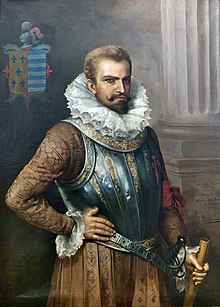 Painting of a bearded man in early 16th-century attire including prominent ruff collar, wearing a decorative breastplate, with his right hand resting on his hip and his left hand grasping a cane or riding crop.