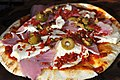 Pizza with ham, mozzarella, olives and pepperoni.jpg