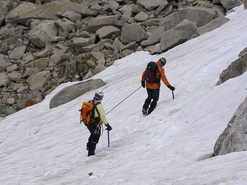Deux alpinistes encordés progressant sur une pente de neige, corde tendue
