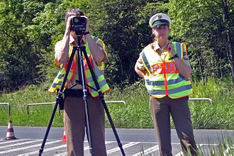Speed limit enforcement - Police officers in Bavaria checking speed with a tripod-mounted LIDAR speed gun.