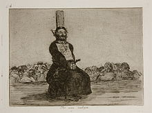A bearded man in clerical vestments tied to a stake on a platform. He is squatting and his hands are bound; in the background is a large group of people, standing below the platform, with indistinct faces.