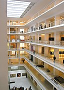 Vue de l'intérieur d'un édifice (un musée): les nombreux étages sont ouverts sur une zone centrale; les tons sont blancs et l'ensemble lumineux.