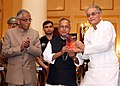 Pranab Mukherjee receiving the Book of Bengali short stories 'Galpanjali', composed by late Dr. Debranjan Mukhopadhyay from the former Governor of West Bengal, Shri Shyamal Sen, at a function.jpg