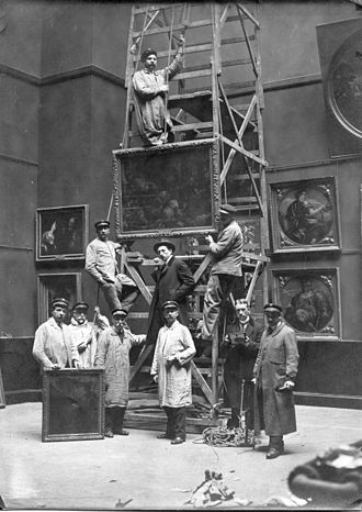 In the center of the picture, Emile Theodore (museum curator of the Palace of Fine Arts in Lille (museum) from 1912 to 1937), here during reconstruction of the gallery dedicated to Spanish and Italian paintings, two years after the end of the First World War Reaccrochage de la salle IItalie-Espagne apres la guerre 1914-1918.jpg