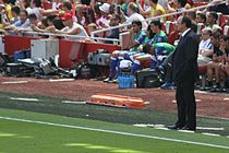 A coloured photograph of manager Rafael Benítez standing on the stadium touchline.