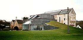 A large glass conservatory is shown attached to a house in a field.