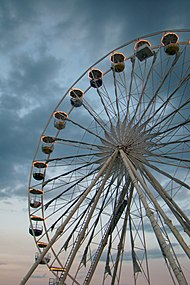 View of a Ferris wheel with white structure during twilight.