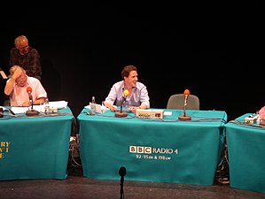 "I'm Sorry I Haven't a Clue -  Rob Brydon (centre) chairs the Newcastle recording of I'm Sorry I Haven't a Clue. Also pictured are Tim Brooke-Taylor (low left) and Colin Sell (top left). The chair next to Brydon with the microphone is 'used' by ""Samantha"""