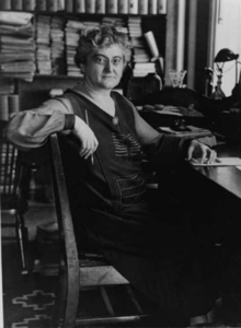 Black and white photograph of a woman in a library, seated at a desk with her arm draped over a chair, holding a pencil in her right hand