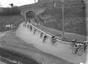 Goulburn to Sydney Classic - A line of cyclists coming through the arch of the railway bridge at Picton