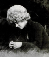A young woman with blonde curly hair, wearing dark clothing and sitting on grass