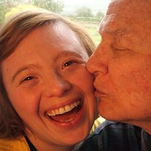Close up of Sarah Gordy smiling while her dad gives her a peck on the cheek