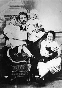 Photograph of a seated man holding two toddlers. At his feet sits a child's rattan rocking chair and a young girl clutching a doll.