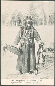 "Faded black and white photo of a Mongol Buryat shaman, a masked man wearing a thick robe, an apron covering his chest, and a round hat with covering his face down to his nose. He is holding a drum in his right hand, and two decorated wooden sticks in his left hand. The caption in Russian and French means ""Buryat shaman."""