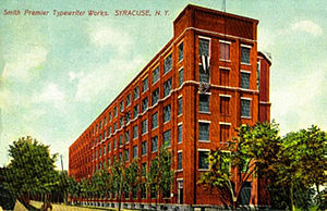 Smith Corona - Smith Premier Typewriter Co. at Syracuse, New York c.1910 – The Smith Premier factory seen here was begun in early March 1903 and was completed in about four months. The factory was shut down around 1921 when the Smith Premier Typewriter Company was absorbed fully by Remington Typewriter Company. This is the street side view; powerhouse and rail spur are behind, on the right out of view.