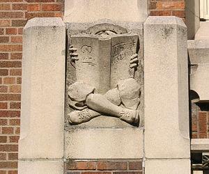 English: Concrete relief of a boy reading a bo...
