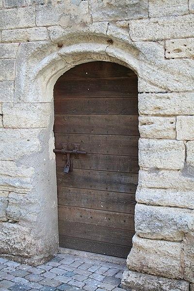 """Saint-Thibéry (Hérault, France) - Porte de la Tour de l'abbaye, avec son célèbre verrou: """"Qui embrasse ce verrou, se marie dans l'année""""."""