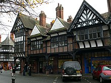 A row of shops seen at an angle with an arcade at ground level.  Above this the building is timber-framed, with four gables; the lateral two of these have painted plaster panels and decorated timber framing within the gable, and the central gables contain brick nogging and pargeting.