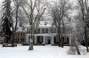 A snow-covered two story house with dormer windows on the roof and a porch on the ground floor. The stone house has several large trees in front.