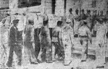 A line of men carrying a casket