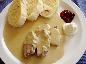 Czech cuisine - Svíčková na smetaně served with dumplings, whipped cream and cranberries