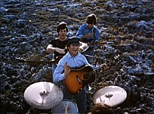 The Beatles performing music in the field. In the foreground, the drums are played by Starr (only the top of his head is visible). Beyond him, the other three stand in the column with air guitars. In the rear, Harrison, head down, strikes the chord. In the front, Lennon smiles and gives the little wave toward camera, holding his pick. Between am, McCartney is jocularly about to choke Lennon.