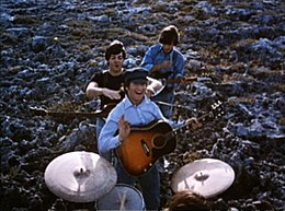 The Beatles performing music in a field. In the foreground, the drums are played by Starr (only the top of his head is visible). Beyond him, the other three stand in a column with their guitars. In the rear, Harrison, head down, strikes a chord. In the front, Lennon smiles and gives a little wave towards camera, holding his pick. Between them, McCartney is jocularly about to choke Lennon.