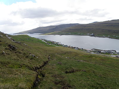 Trongisvagsfjordur seen from the northern side of the fjord, from the hiking path to Hvannhagi. Krambatangi ferry port and the Saltsilo on Drelnes are visible. Trongisvagsfjordur and Tvoroyri Faroe Islands.JPG