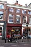 foto van =Rechterhelft van zeer breed huis met twee bouwlagen, een kelder en een zadeldak loodrecht op de straat