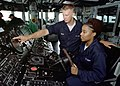 US Navy 000708-N-7412M-011 Seaman Jody Bean from Russell, MA, shows Midshipman 1st Class Latoyia Hill the bearing indicator on the ship's helm.jpg