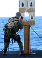 US Navy 030205-N-4154B-502 Electronics Technician 1st Class Lawerence from Tulsa, Okla., grades the target of his shipmates after shooting for weapons qualifications.jpg