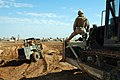US Navy 041113-N-5386H-030 Perched on the blade of a bulldozer, Lt. James Golden, assigned to Naval Mobile Construction Battalion Two Three (NMCB 23), supervises excavation operations at a barrow pit.jpg