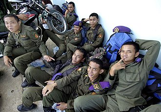 Etiquette in Indonesia - Most Indonesians initiate social contact with a smile, it is a sign that you are approachable, such as shown here by military personnel in Aceh.