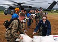 US Navy 050124-N-0168J-001 Marine Cpl. Tyler Samms, and Fire Controlman 3rd Class Bethany A. Deadman pass bags of rice to fellow Sailors and Marines during a joint working party with foreign forces at an airfield in Sabang, Ind.jpg
