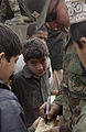 US Navy 051121-F-2729L-004 U.S. Navy 1st Class Manuel Baca, assigned to Naval Mobile Construction Battalion Seven Four (NMCB-74), signs a cricket bat that he made for children at Jabba Farm Tent Village in Shinkiari, Pakistan.jpg