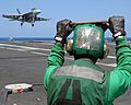 US Navy 070710-N-8923M-192 Aviation Boatswain's Mate Equipment Airman Benjamin Shaw stands by to lead the arresting wire back into the flight deck as an F-A-18F Super Hornet prepares to make an arrested recovery.jpg