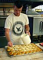 US Navy 070829-N-7163S-005 Storekeeper 1st Class Daniel Scott from Navy Operational Support Center (NOSC) Cincinnati prepares biscuits at the Walnut Hills soup kitchen prior to serving lunch to underprivileged citizens of the g.jpg