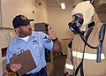 US Navy 080910-N-4649C-003 Machinist's Mate 1st Class Steven Perry, an instructor at the the advanced firefighting school at Trident Training Facility, Bangor at Naval Base Kitsap, ensures a Sailor is properly dressed in a fire.jpg