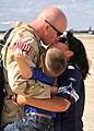 US Navy 100904-N-9565D-065 Aviation Structural Mechanic 2nd Class William Thompson eceives a hug and kiss from his wife and son during a homecoming.jpg