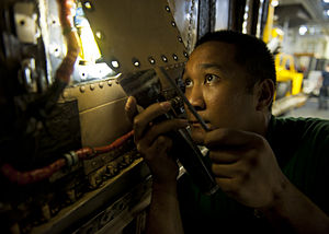 US Navy 120204-N-BT887-178 Aviation Structural Mechanic (Equipment) 3rd Class Jasper Cruz searches for a screw in the engine compartment of an F-A.jpg