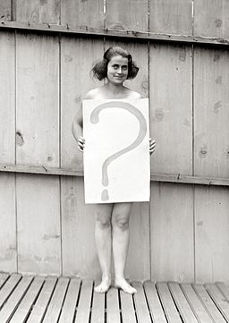 Unclothed woman behind question mark sign