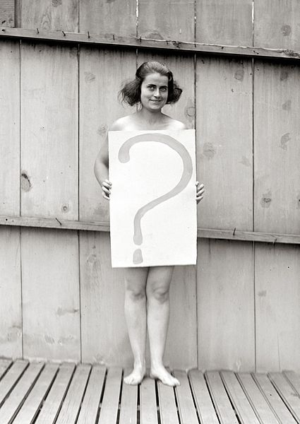 File:Unclothed woman behind question mark sign.jpg
