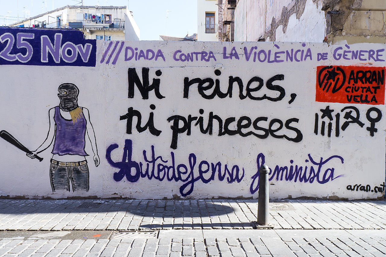 Painted on a white wall, graffiti of a person wearing a tank top and mask and holding a bat, under and next to the words: