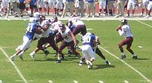 Hráči se střetnou u řady rvačky jako quarterback připravuje projít míč