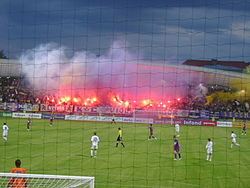 A football stadium full of supporters, which are using flares and smoke bombs.