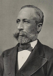Head and shoulders photograph of a man in a Victorian suit.  He has a beard, a large mustache and is slightly balding.  He wears a serious expression and is looking slightly to the right.