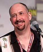 A balding, middle aged caucasian male looks slightly to the left with a smile. He is wearing a black and cream shirt with palm tree images upon it.