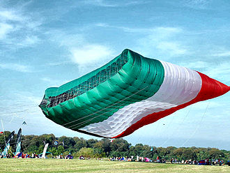 Peter Lynn - The World's Largest Kite (2005–),  the Flag of Kuwait. Area: 1019 m². Collapsed weight: 200 kg. Volume: 4500 cubic m. Super-ripstop nylon. Construction time: 750 hours.