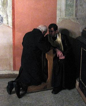 Sacrament of Penance - A penitent confessing his sins in the formerly Latin Church Catholic, now Ukrainian Byzantine Rite Greek-Catholic church of the Bernhardines in Lviv, Ukraine.